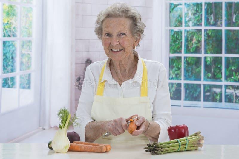 Femme supérieure heureuse faisant cuire dans la cuisine photo libre de droits