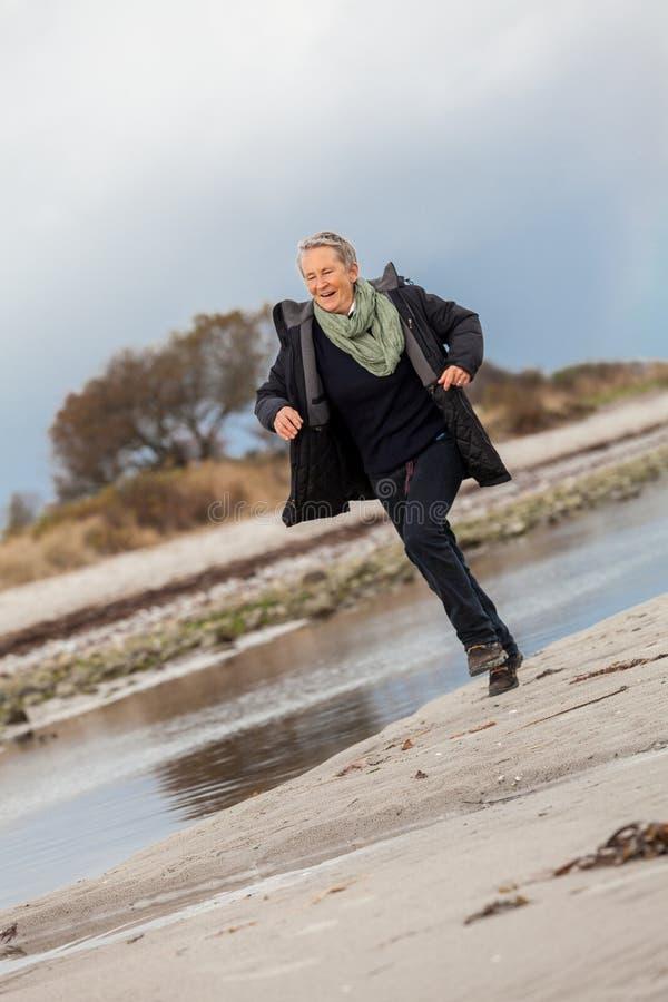 Femme supérieure heureuse gambadant sur la plage image libre de droits