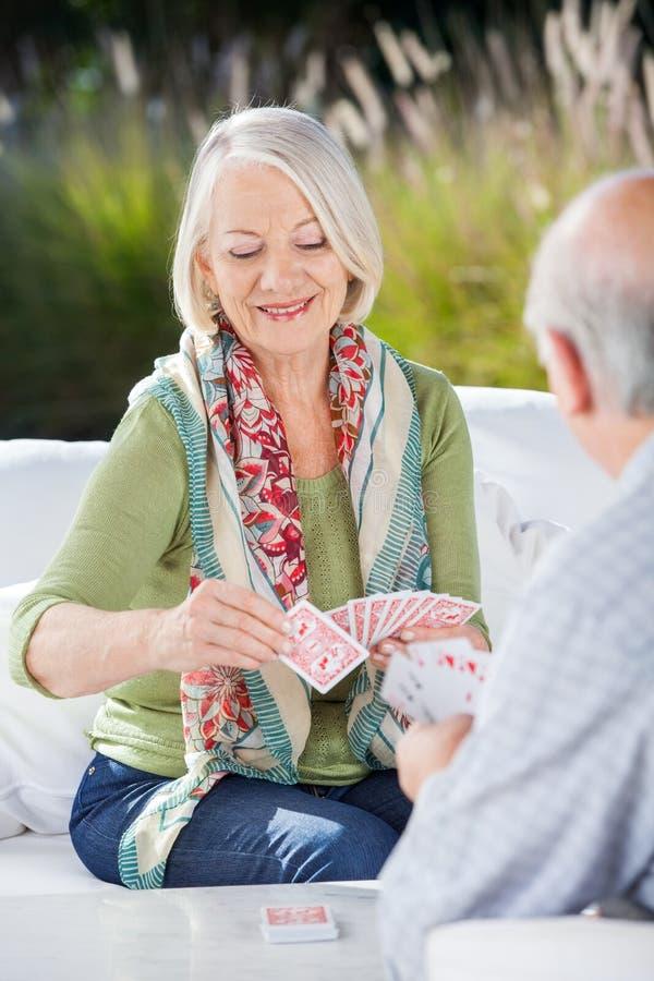 Femme supérieure heureuse jouant des cartes avec l'homme image libre de droits
