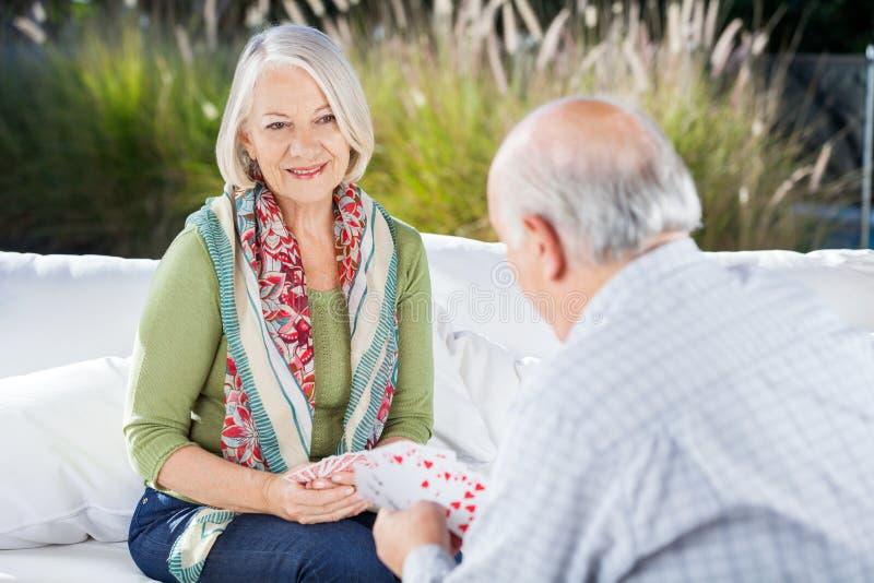 Femme supérieure heureuse jouant des cartes avec l'homme photographie stock libre de droits