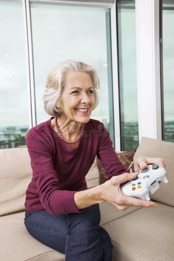 Femme supérieure heureuse jouant le jeu vidéo sur le sofa à la maison images stock