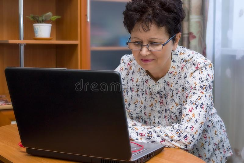 Femme supérieure heureuse mignonne avec des lunettes fonctionnant avec le carnet à la maison photo stock