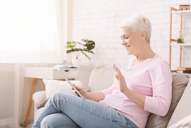 Femme supérieure heureuse parlant avec la famille par l'intermédiaire du comprimé numérique image stock