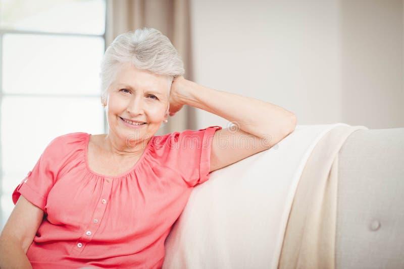 Femme supérieure heureuse s'asseyant sur le sofa photo libre de droits