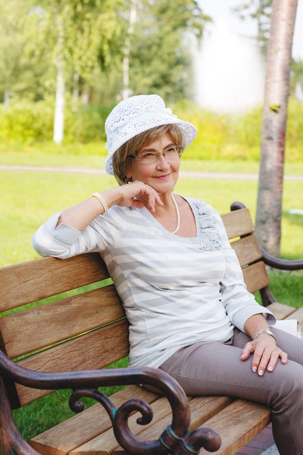 Femme supérieure heureuse s'asseyant sur un banc photographie stock