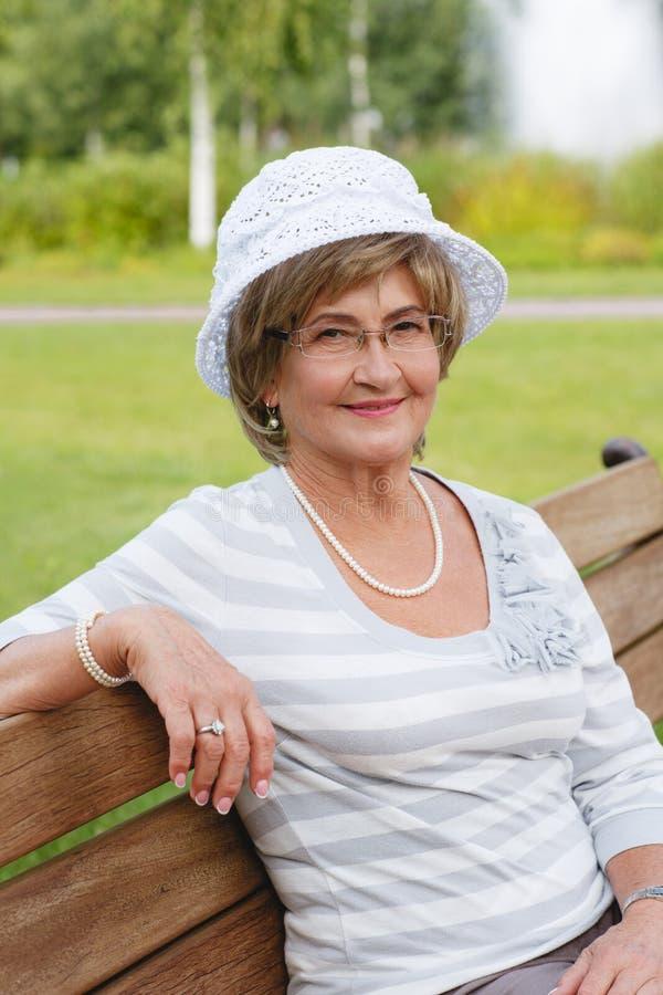 Femme supérieure heureuse s'asseyant sur un banc photos stock