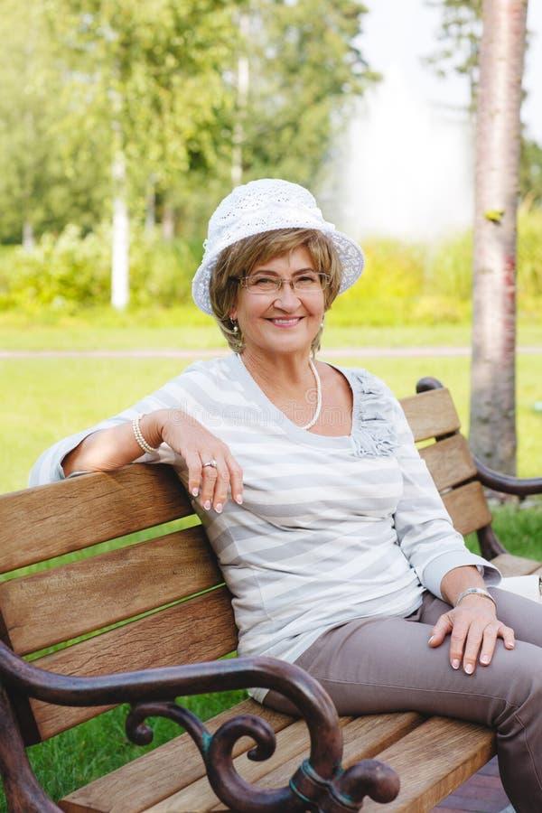Femme supérieure heureuse s'asseyant sur un banc images stock