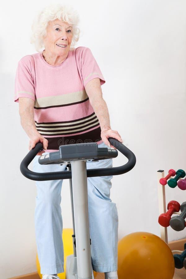 Femme supérieure heureuse s'exerçant sur le vélo photos stock