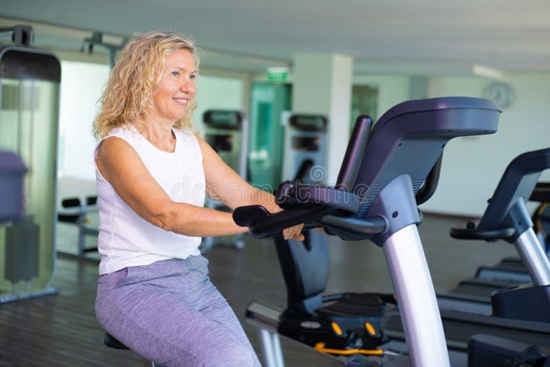 Femme supérieure heureuse s'exerçant sur le vélo dans le gymnase image libre de droits