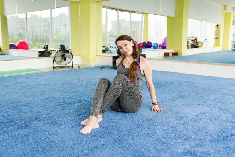 Femme supérieure heureuse se reposant sur le tapis après exercice dans le gymnase photos stock