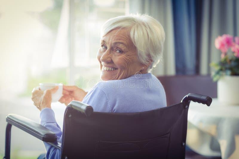 Femme supérieure heureuse sur le fauteuil roulant tenant une tasse de thé images stock