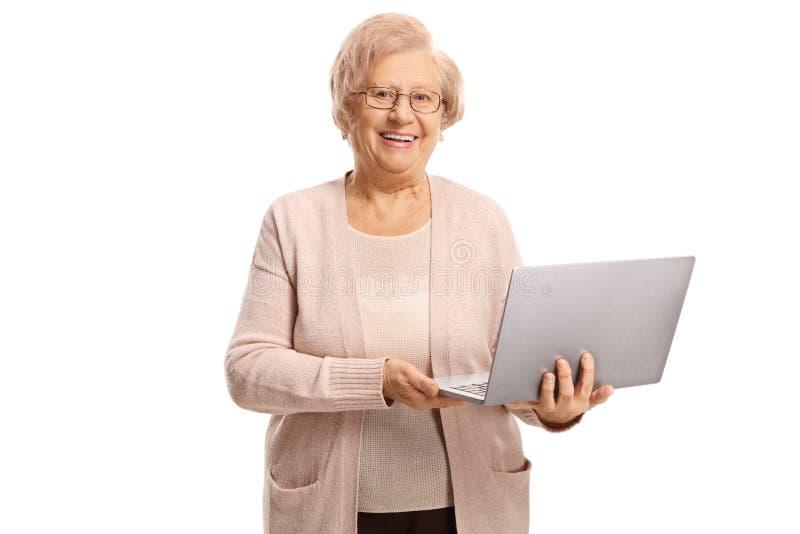 Femme supérieure heureuse tenant un ordinateur portable image stock