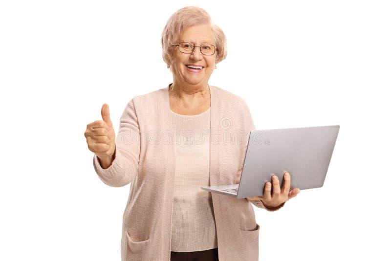 Femme supérieure heureuse tenant un ordinateur portable et montrant des pouces  image libre de droits