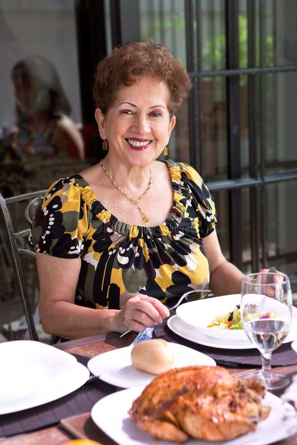 Femme supérieure hispanique appréciant l'heure du déjeuner extérieure dans un environnement familial image stock