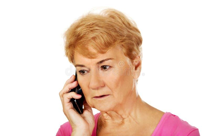 Femme supérieure inquiétée parlant par le téléphone image stock