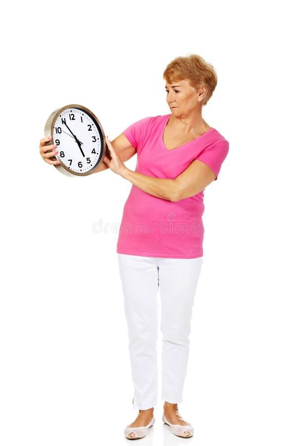 Femme supérieure inquiétée tenant la grande horloge photos libres de droits