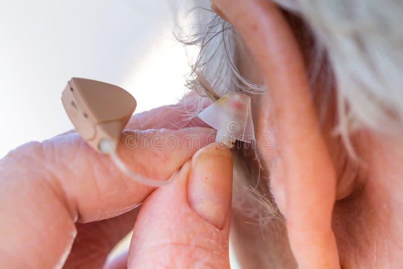 Femme supérieure insérant la prothèse auditive dans des ses oreilles photographie stock libre de droits