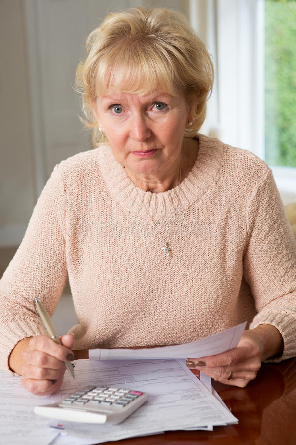 Femme supérieure intéressée passant en revue des finances domestiques image stock