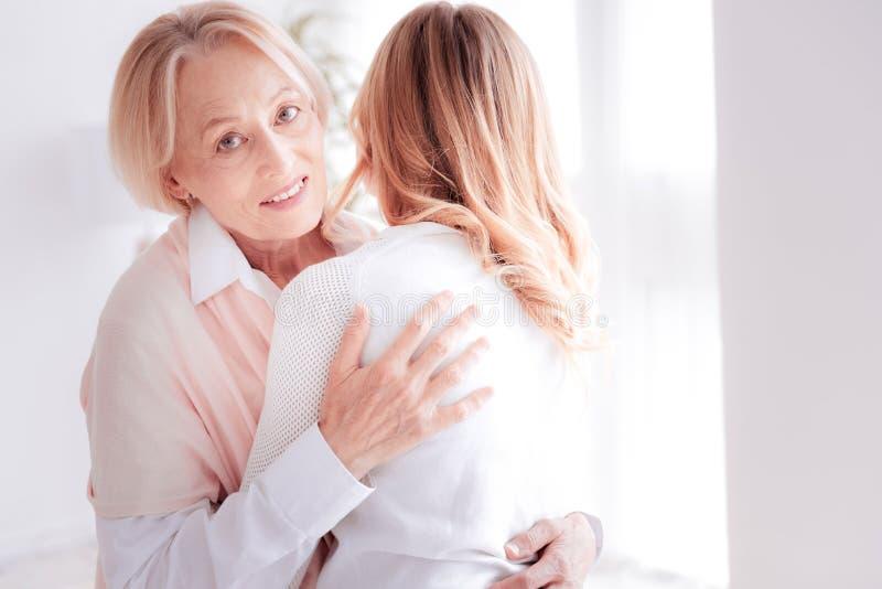 Femme supérieure joyeuse étreignant sa fille adulte photographie stock