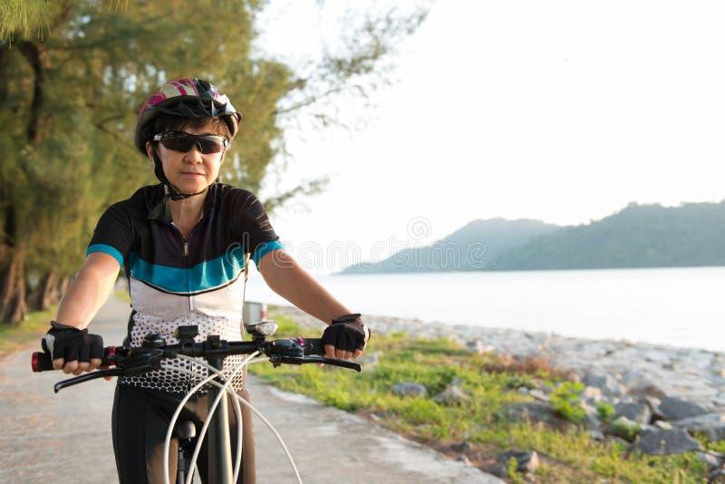 Femme supérieure joyeuse montant une bicyclette photos libres de droits