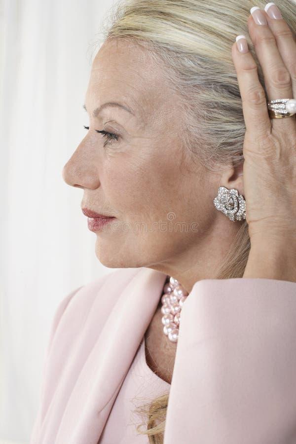 Femme supérieure jugeant des cheveux arrières photo stock