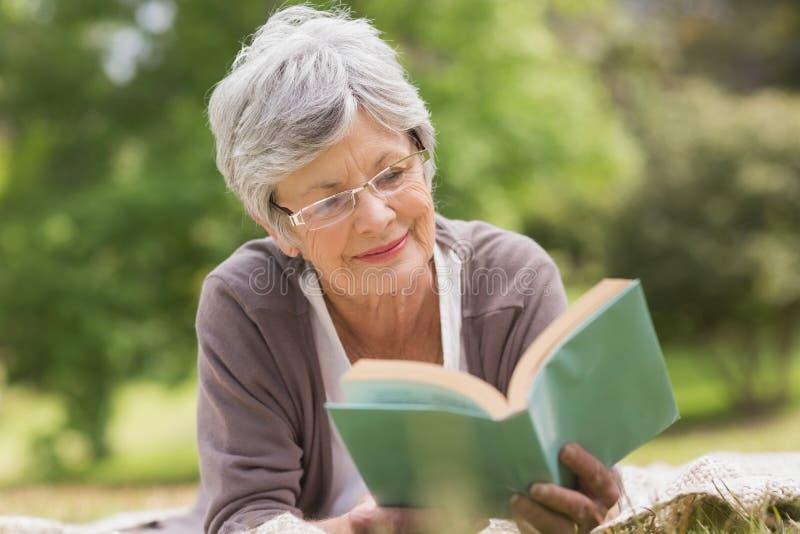 Femme supérieure lisant un livre au parc photo stock