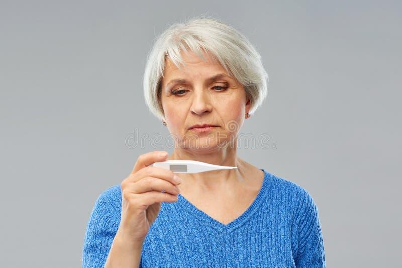 Femme supérieure malade avec le thermomètre images libres de droits