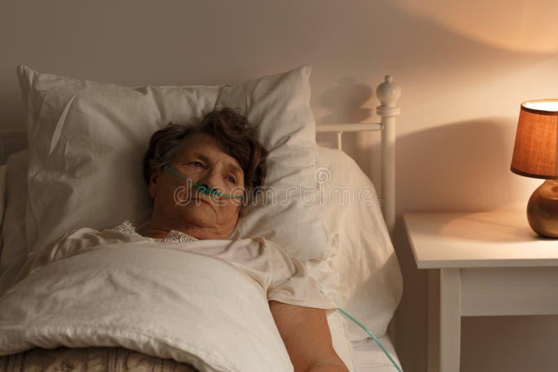 Femme supérieure malade dans le lit photos libres de droits