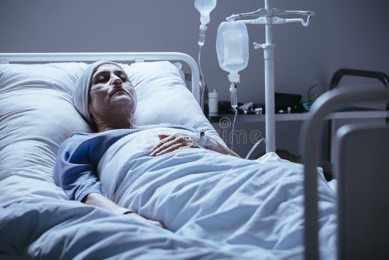 Femme supérieure malade et seule avec la leucémie pendant la chimiothérapie i images stock