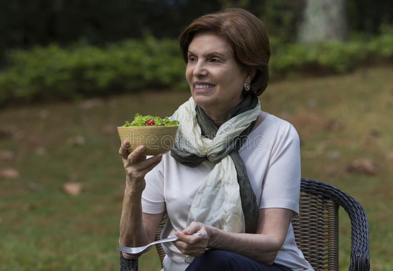 Femme supérieure mangeant d'une salade dans un jardin image libre de droits