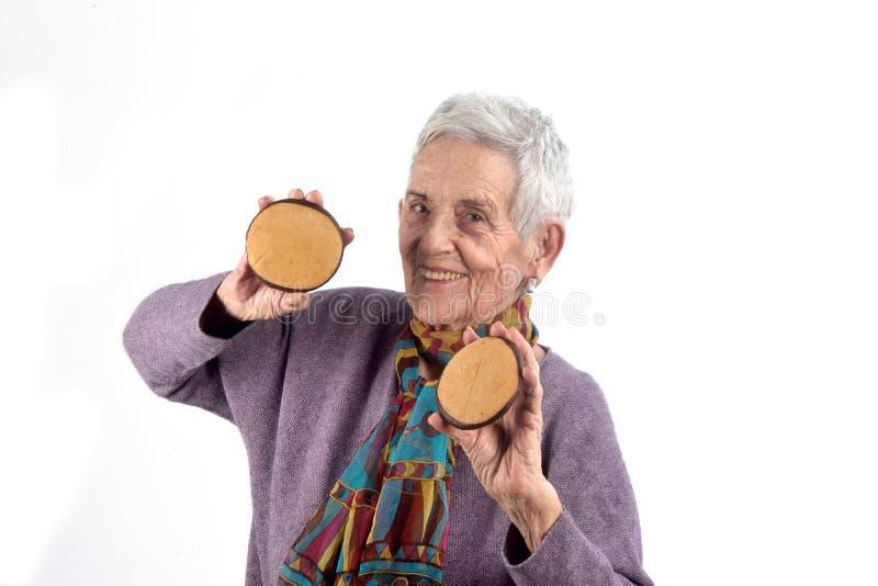Femme supérieure mangeant le biscuit sur le fond blanc photos stock