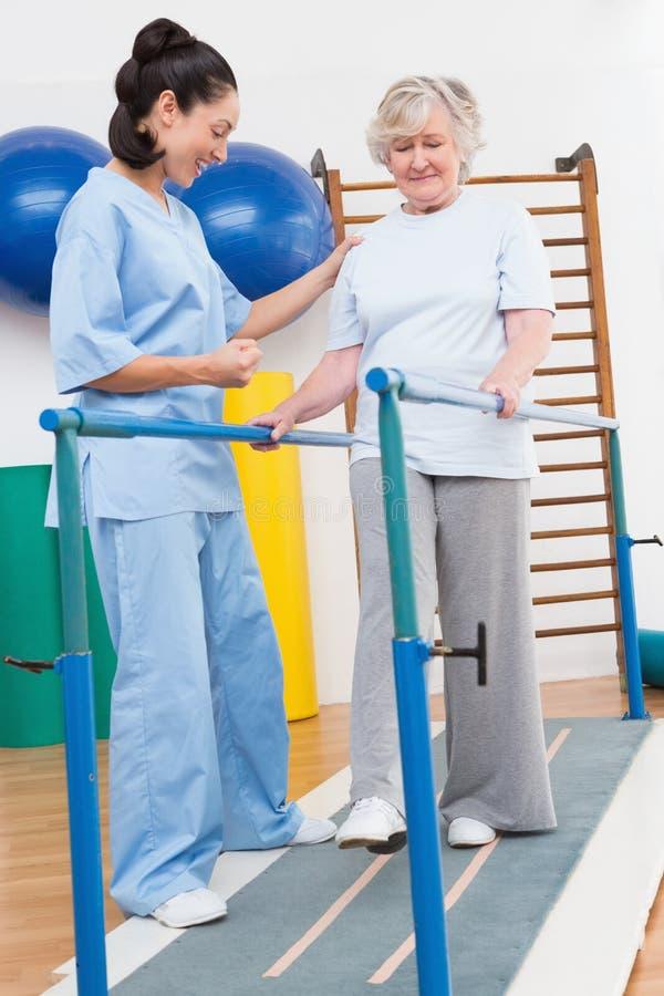 Femme supérieure marchant avec des barres parallèles avec le thérapeute image libre de droits