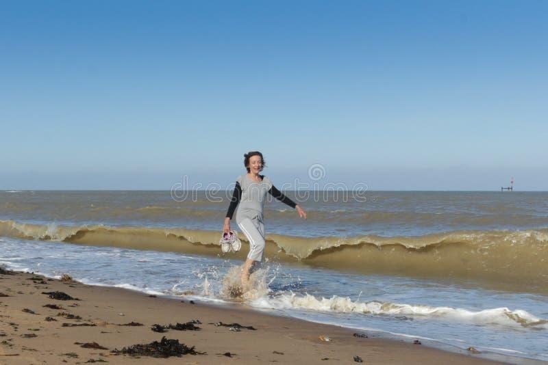 Femme supérieure marchant en mer image stock