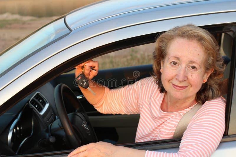 Femme supérieure montrant sa nouvelle voiture photographie stock