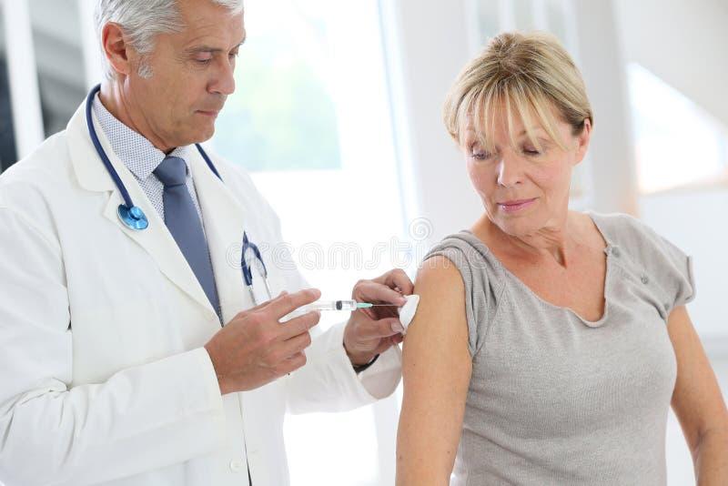 Femme supérieure obtenant vaccinée image stock