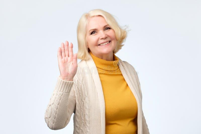 Femme supérieure ondulant sa main indiquant le bonjour à son ami photographie stock libre de droits