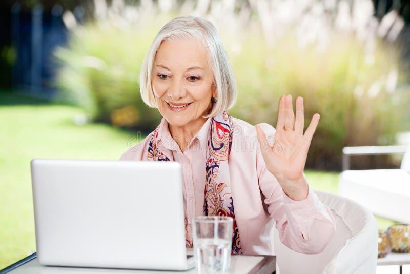 Femme supérieure ondulant tandis que vidéo causant sur l'ordinateur portable images libres de droits