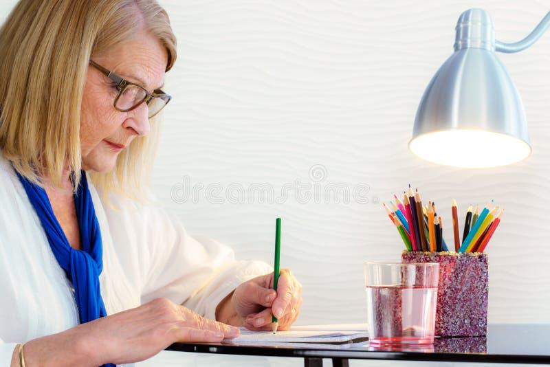Femme supérieure passant le temps avec livre de coloriage photographie stock libre de droits