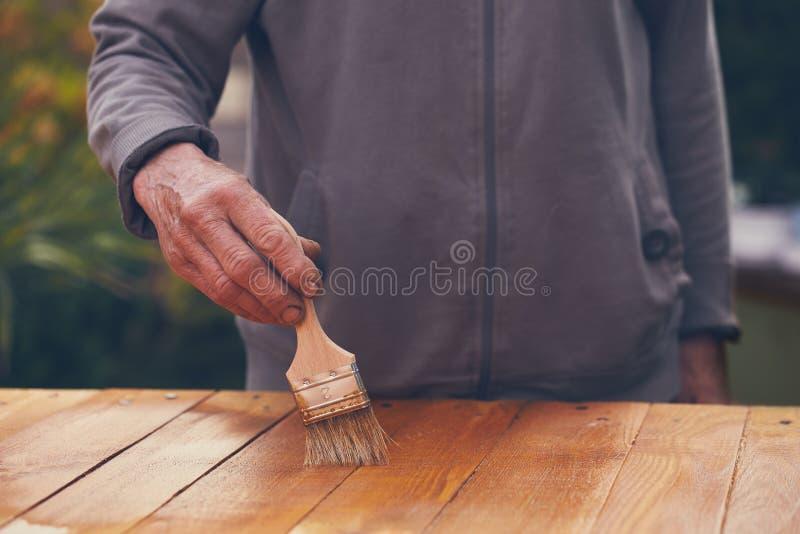 Femme supérieure peignant une table en bois photo stock