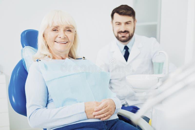 Femme supérieure positive voyant le dentiste image stock