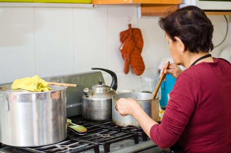 Femme supérieure préparant la nourriture saine des légumes frais photo stock