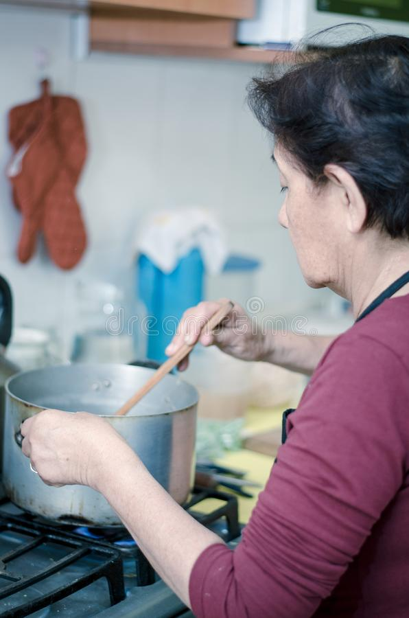 Femme supérieure préparant la nourriture saine des légumes frais images stock