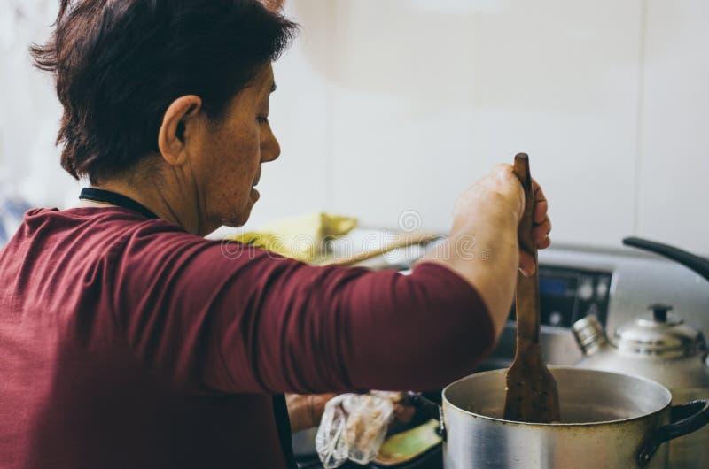 Femme supérieure préparant la nourriture saine des légumes frais photographie stock