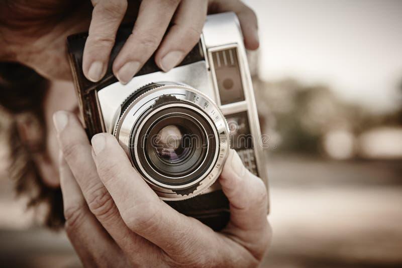 Femme supérieure prenant des photos avec l'appareil-photo de vintage Voyage photographie stock