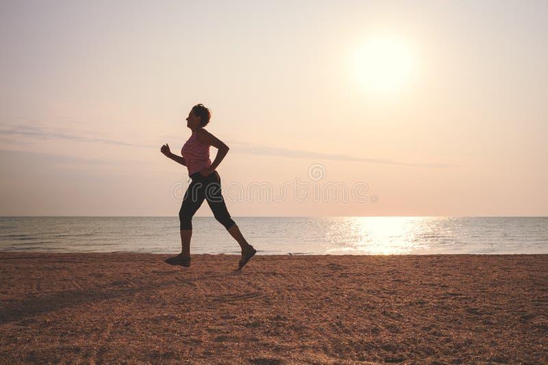 Femme supérieure pulsant sur la plage de mer photographie stock libre de droits