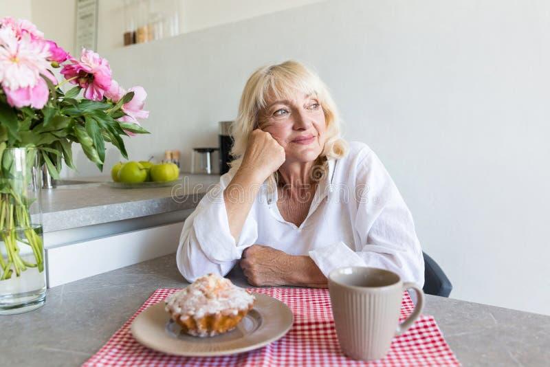 Femme supérieure réfléchie s'asseyant à la table de cuisine photographie stock