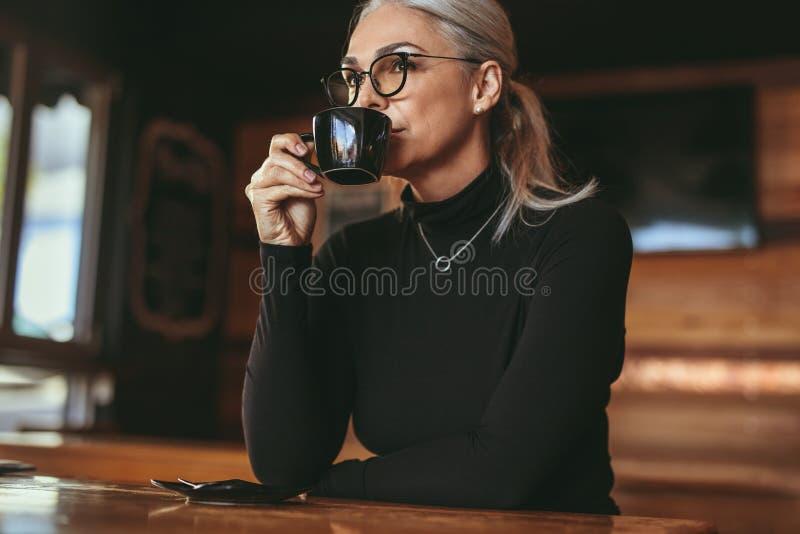 Femme supérieure réfléchie s'asseyant au café potable de café photos stock