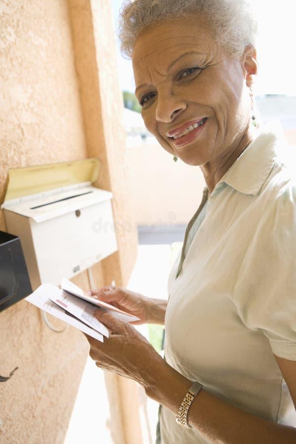 Femme supérieure rassemblant la lettre de la boîte aux lettres photo libre de droits