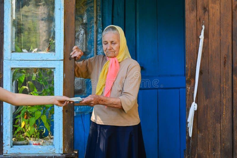 Femme sup?rieure recevant l'argent de retraite sur le porche pr?s de sa maison La grand-m?re tient l'argent image stock