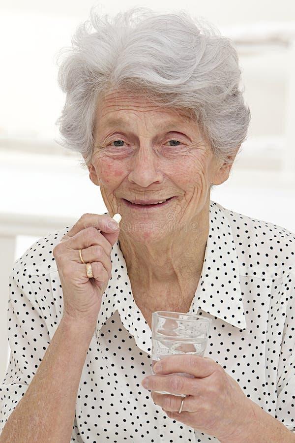 Femme supérieure recevant le médicament photo stock